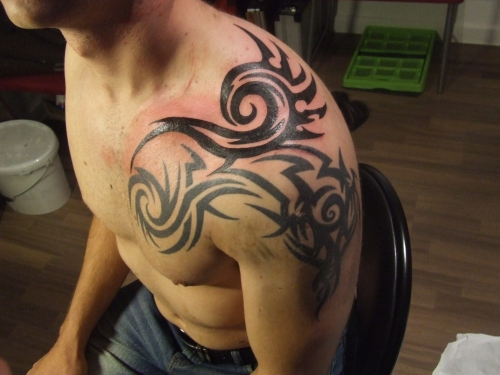 Tribal Shoulder And Chest Tattoo